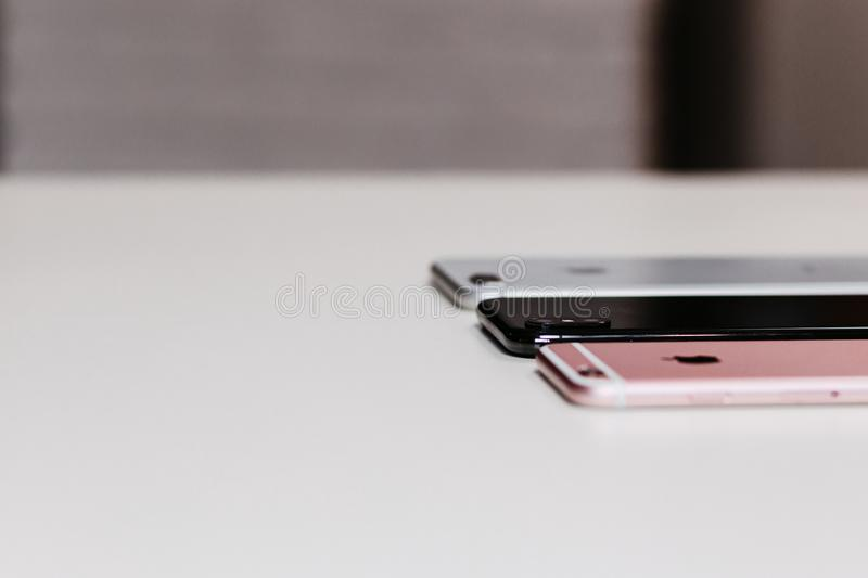 Three Assorted-color Iphone on White Wooden Desk royalty free stock image