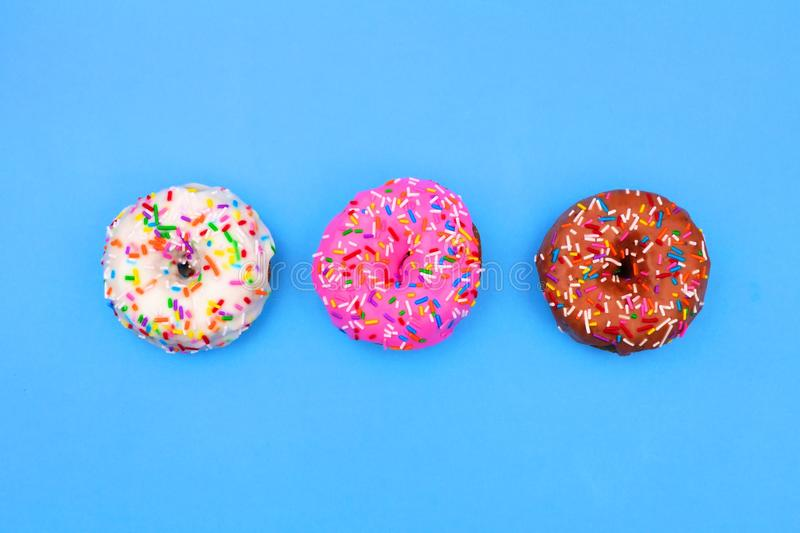 Three assorted donuts with pastel icing against a soft blue background stock image