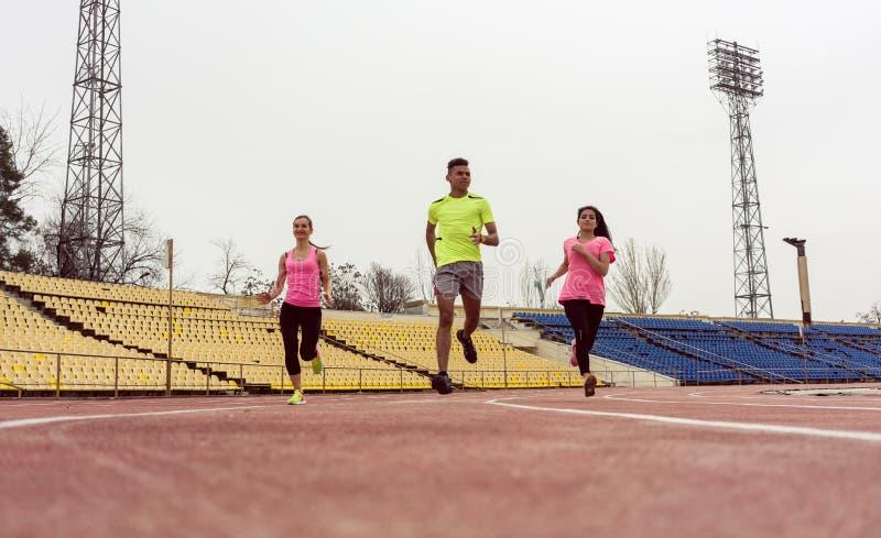 People running on ground. Three athlete people running in speed on sport ground stock image