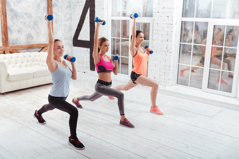 Three athletic women doing lunges in gym royalty free stock photos