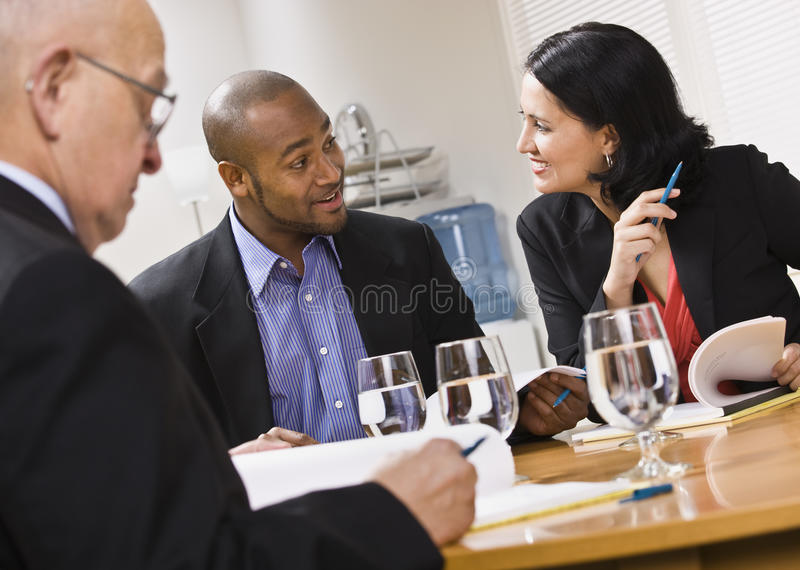 Three attractive business people with water. Three attractive business people sitting at a table with water and paperwork. Horizontal stock photo