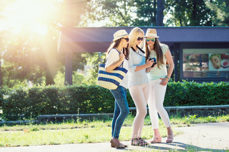 Three attractive girls looking at photos on their camera at summer holidays. Girl friends on their travel vacation royalty free stock photo