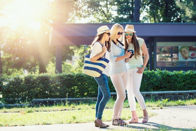 Three attractive girls looking at photos on their camera at summer holidays royalty free stock photo