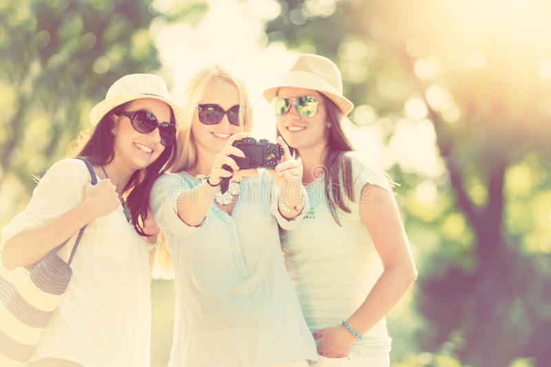 Three attractive girls taking picture at summer holidays royalty free stock images