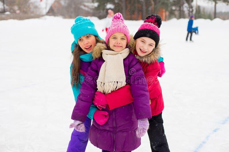 Three attractive skater girl hug on the ice stock image