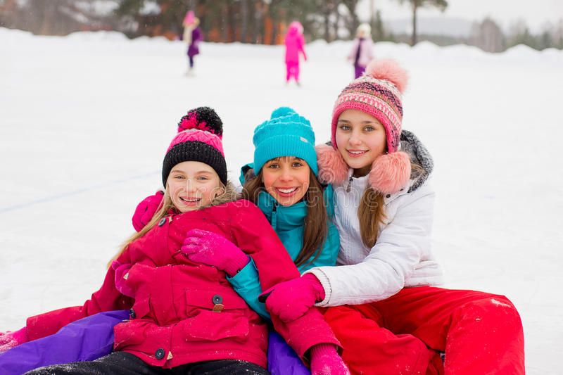 Three attractive skater girl sitting on the ice royalty free stock images