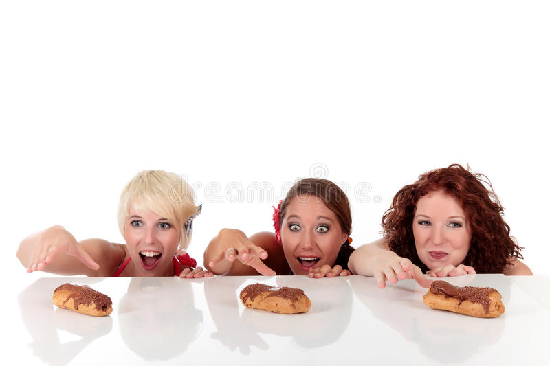 Three attractive young woman longing eyes. Three attractive young women looking with longing eyes, ready to take the eclairs from table. Studio shot. White stock photos