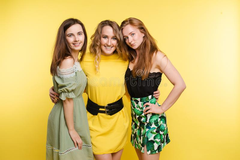 Three attractive young woman posing together  at yellow studio background stock photos
