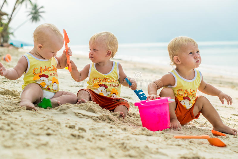 Three baby Toddler sitting on a tropical beach in Thailand and playing with sand toys. The yellow shirts. Two boys and one girl stock images