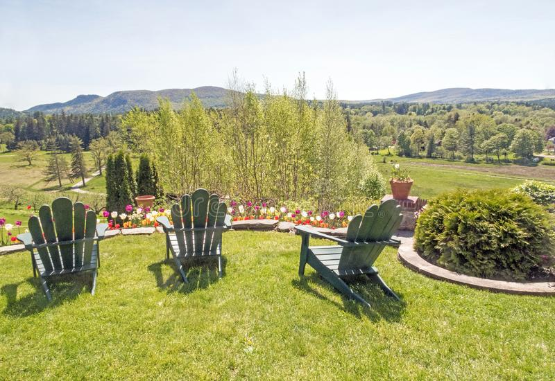 Adirondack chairs on grass lawn overlooking Berkshires. Three backlit empty green Adirondack chairs on grass lawn overlooking view of tulips, garden, field and stock photo