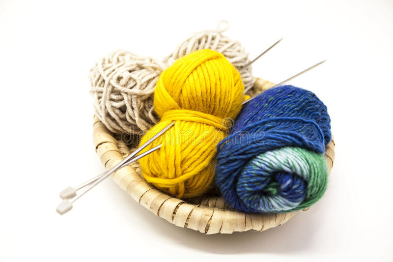 Three ball of woolen threads, yellow, blue, beige and steel knitting needles in a wooden basket on a white background. stock photo