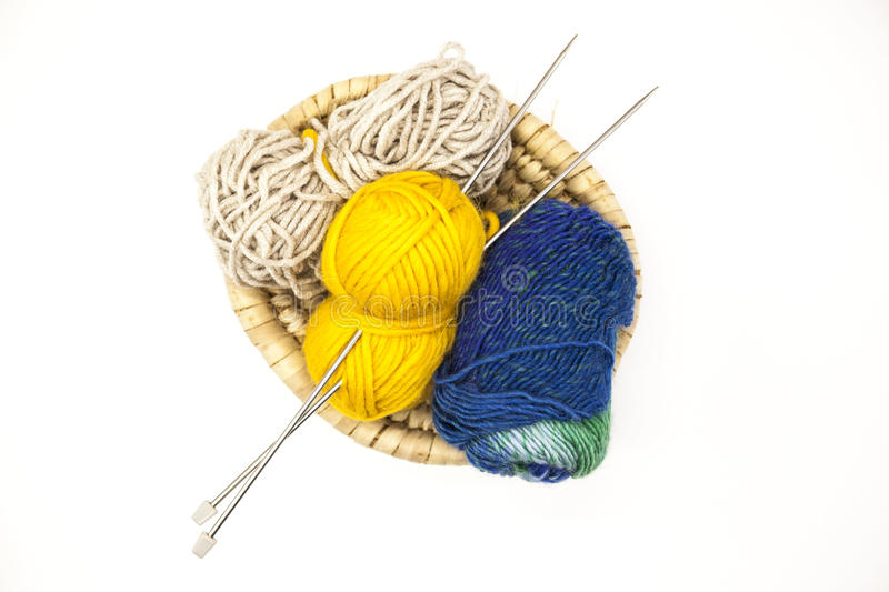 Three ball of woolen threads, yellow, blue, beige and steel knitting needles in a wooden basket on a white background. royalty free stock photo