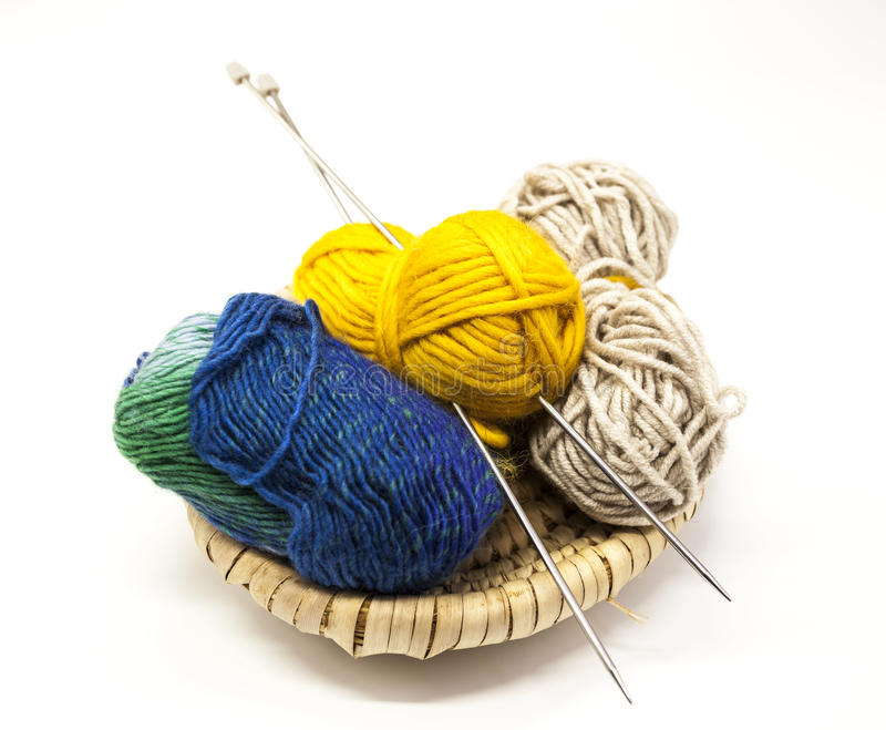 Three ball of woolen threads, yellow, blue, beige and steel knitting needles in a wooden basket on a white background. stock photos