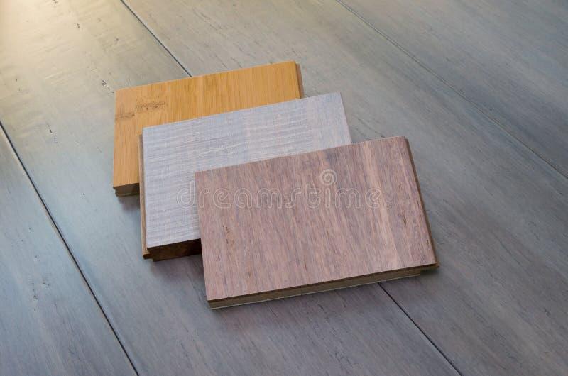 Three Bamboo Flooring Samples. Three tongue and groove bamboo flooring samples laid on top of bamboo flooring planks royalty free stock image