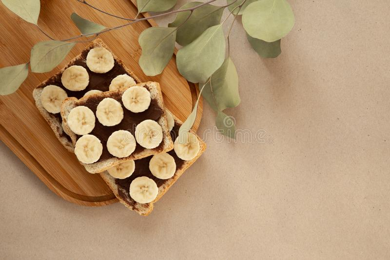 Three banana white bread toasts smeared with chocolate butter that lie on a cutting board with a sprig of leaves on craft paper. Background. top view with area royalty free stock image