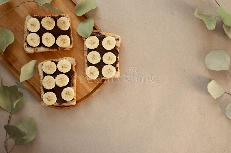 Three banana white bread toasts smeared with chocolate butter that lie on a cutting board with a sprig of leaves on craft paper. Background. top view with area stock photos
