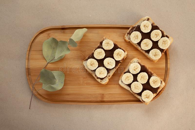 Three banana white bread toasts smeared with chocolate butter that lie on a cutting board with a sprig of leaves on craft paper. Background. top view with area stock image