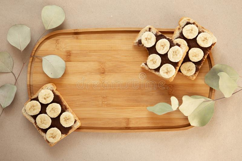 Three banana white bread toasts smeared with chocolate butter that lie on a cutting board with a sprig of leaves on craft paper. Background. top view with area royalty free stock photo