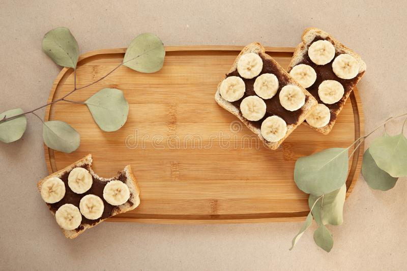 Three banana white bread toasts smeared with chocolate butter that lie on a cutting board with a sprig of leaves on craft paper. Background. top view with area stock images