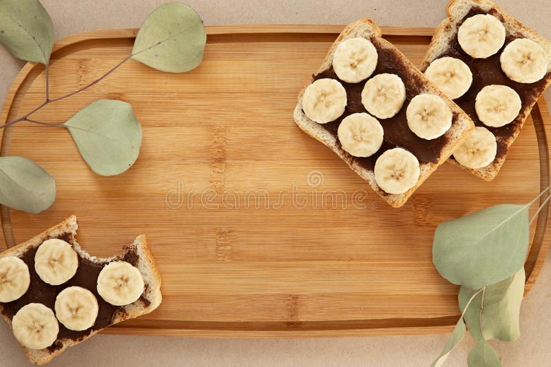 Three banana white bread toasts smeared with chocolate butter that lie on a cutting board with a sprig of leaves on craft paper. Background. top view with area stock photography