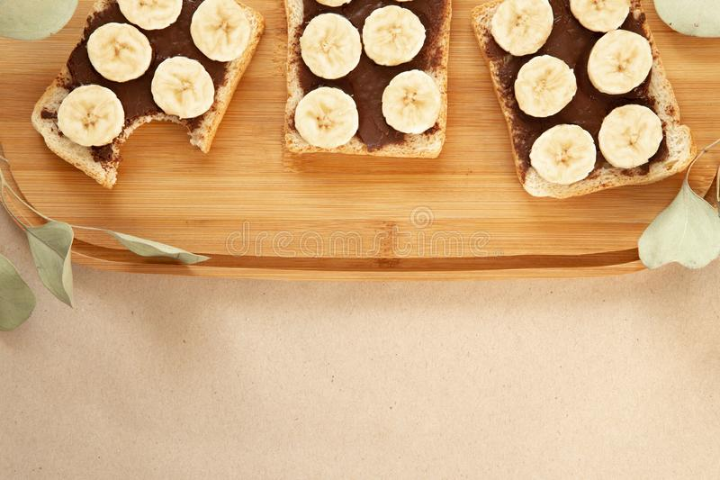 Three banana white bread toasts smeared with chocolate butter that lie on a cutting board with a sprig of leaves on craft paper. Background. top view with area royalty free stock photos