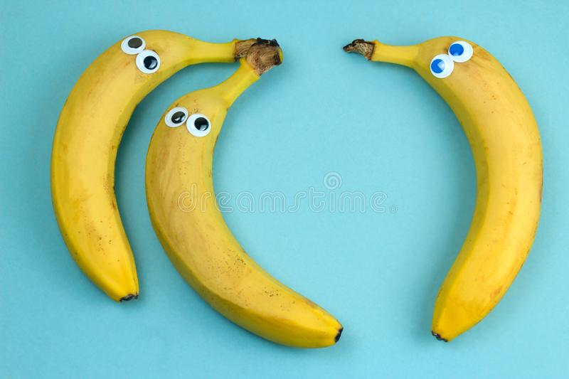 Three bananas with googly eyes. Top view  on a blue background royalty free stock photos