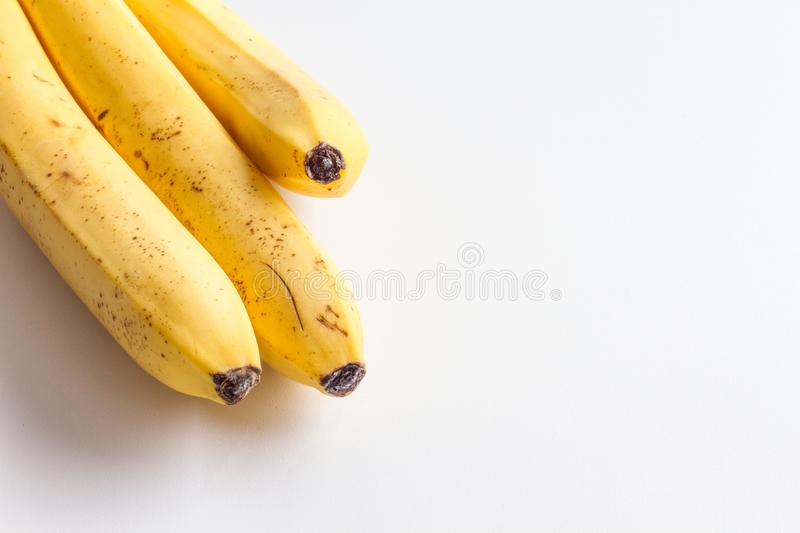 Three Bananas On A White Background In The Corner Frame Of The Photo ...