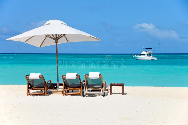 Three beach chairs with white umbrella and yacht at ocean front stock images