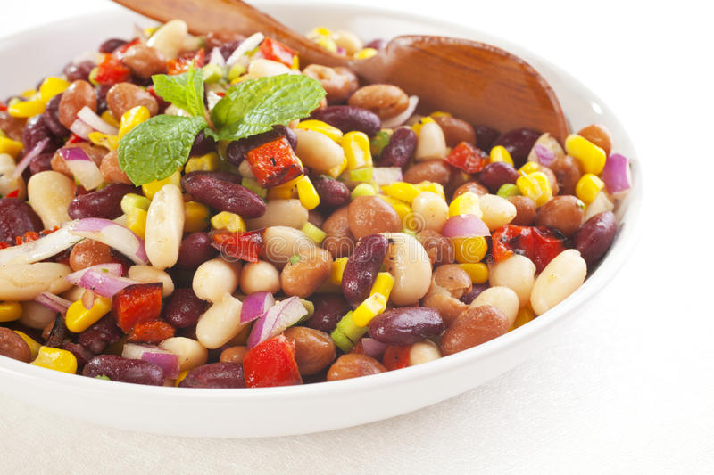 Three Bean Salad. With sweetcorn, roasted red peppers and red onion in a vinaigrette dresing. Focus on foreground royalty free stock photography