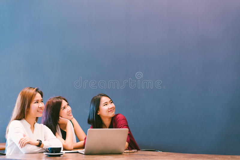 Three beautiful Asian girls looking upward to copy space while working at cafe, modern lifestyle with gadget technology concept stock images