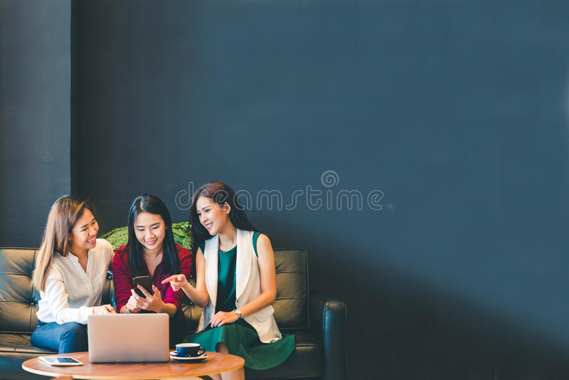 Three beautiful Asian girls using smartphone and laptop, chatting on sofa together at cafe with copy space stock images