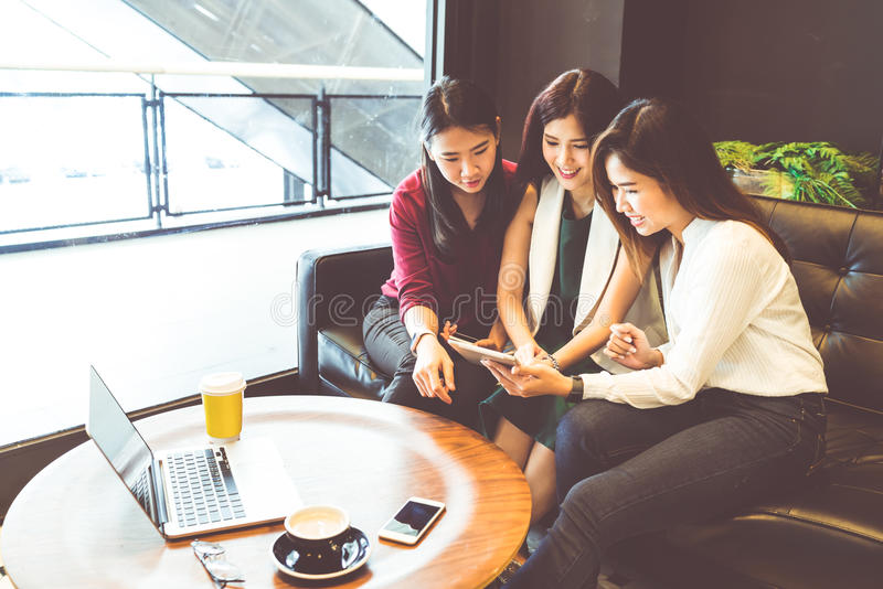 Three beautiful Asian girls using smartphone and laptop, chatting on sofa at cafe. Modern lifestyle with gadget technology or working women on casual business stock photos