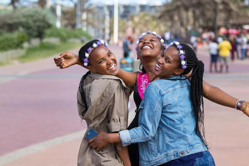 Three beautiful black young women laughing and celebrating a birthday outdoors in Durban, South Africa royalty free stock image