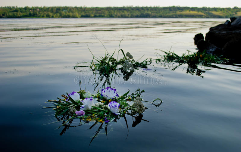 Three beautiful bouquets a wreath of flowers floating along the river calm water of Ivan Kupala. Three beautiful large bouquet of wreaths of white purple yellow stock images
