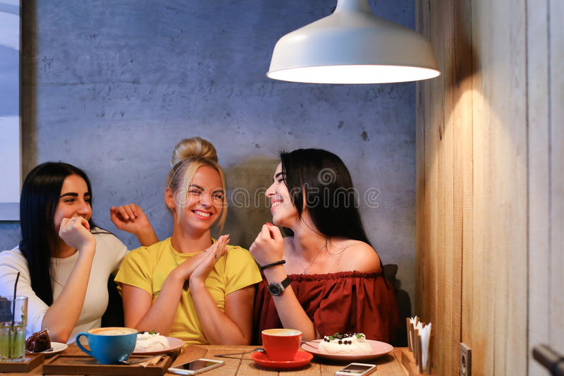 Three beautiful female smile in cafe, talk, tell secrets, eat, d. Concept female friendship, meeting, lunch. Three beautiful women sitting in a cafe smiling royalty free stock photography