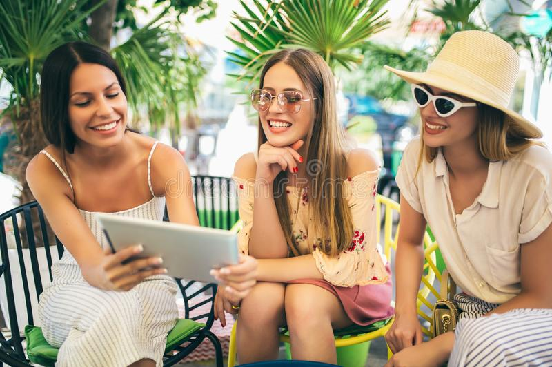 Beautiful friends in a cafe using digital tablet and having fun royalty free stock photos