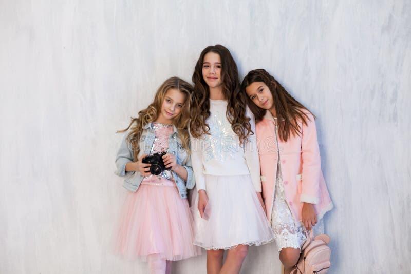 Three beautiful fun fashionable girls in white pink dresses with a camera. Three beautiful fun fashionable girls in white pink dresses at the photo shoot stock photos