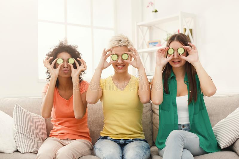 Three beautiful girls covering eyes with cucumber pieces stock photos