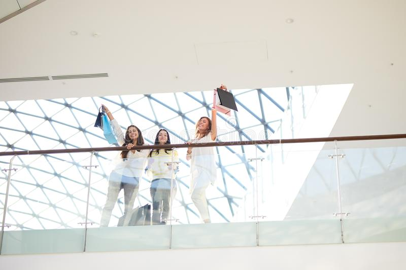 Three beautiful girls dressed in stylish casual clothes holding lots of shopping bags stand on the second floor of a royalty free stock images