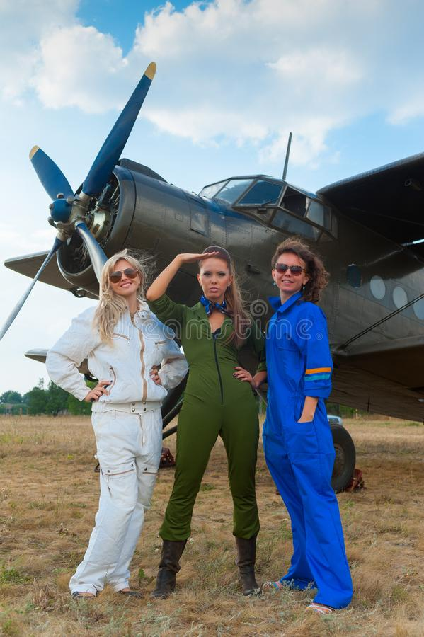 Beautiful girls near the plane. royalty free stock photography