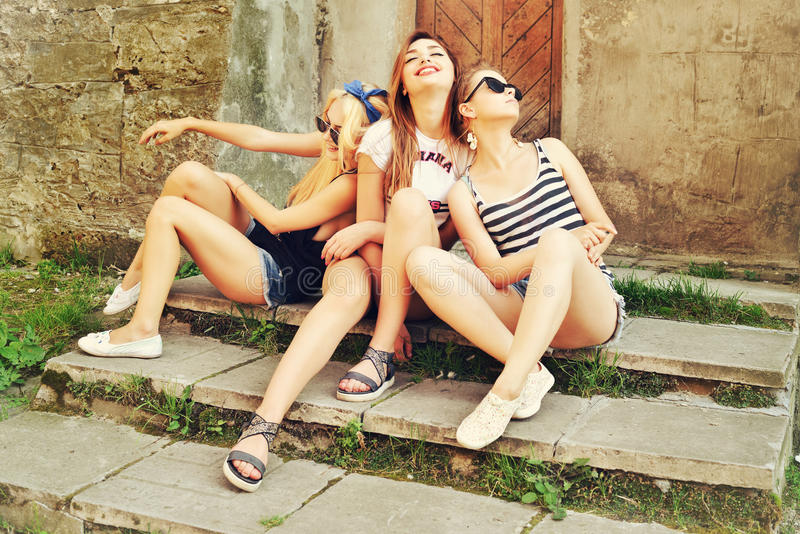 Three beautiful girls rest on the street. Beautiful happy girls in sunglasses on the urban background. Young active people. Outdoo royalty free stock photos