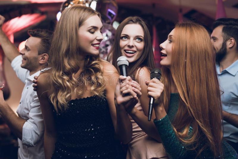 Three beautiful girls sing in a karaoke club. Behind them are men waiting for their turn. stock images
