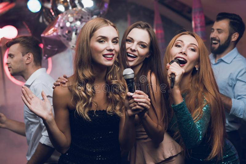 Three beautiful girls sing in a karaoke club. Behind them are men waiting for their turn. Young people have fun in a nightclub stock image