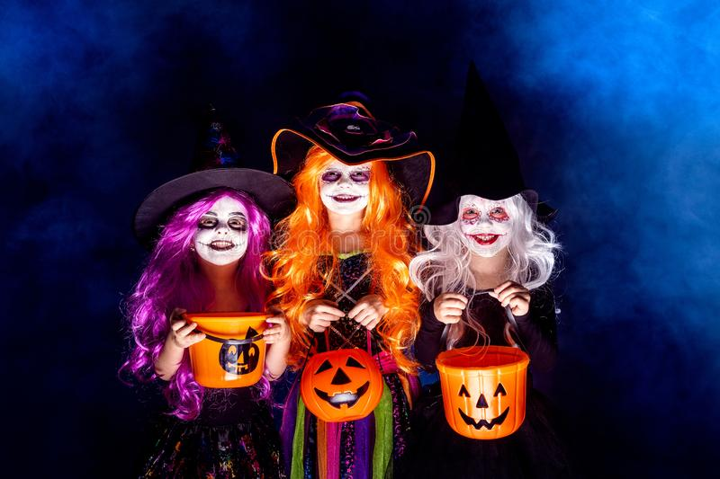 Three Beautiful girl in a witch costume on a dark background in smoke scaring and making faces. Three Beautiful girls in a witch costume on a dark background in stock images