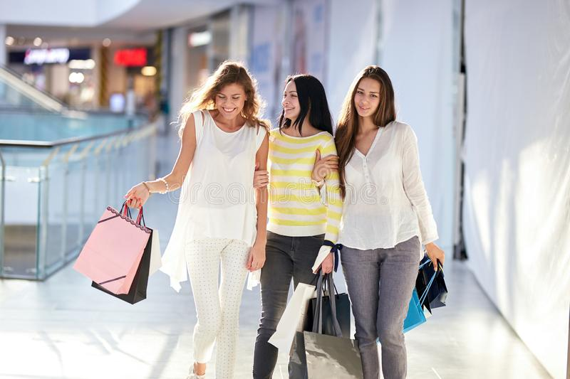 Three beautiful happy girls dressed in nice casual clothes walk with lots of shopping bags in the mall. Shopping time royalty free stock images