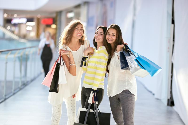 Three beautiful happy girls dressed in nice casual clothes walk with lots of shopping bags in the mall. Shopping time royalty free stock photo