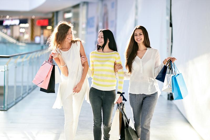 Three beautiful happy girls dressed in nice casual clothes walk with lots of shopping bags in the mall. Shopping time royalty free stock photography