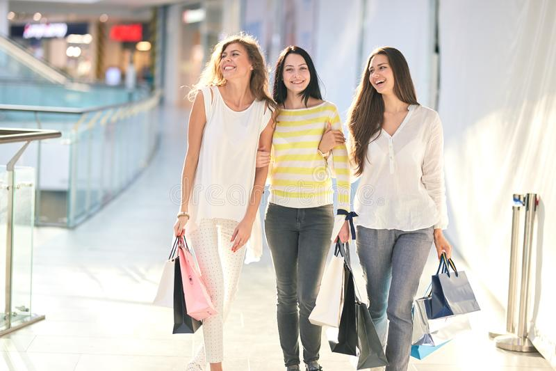 Three beautiful joyful girls dressed in nice casual clothes walk with lots of shopping bags in the mall. Shopping time stock photography
