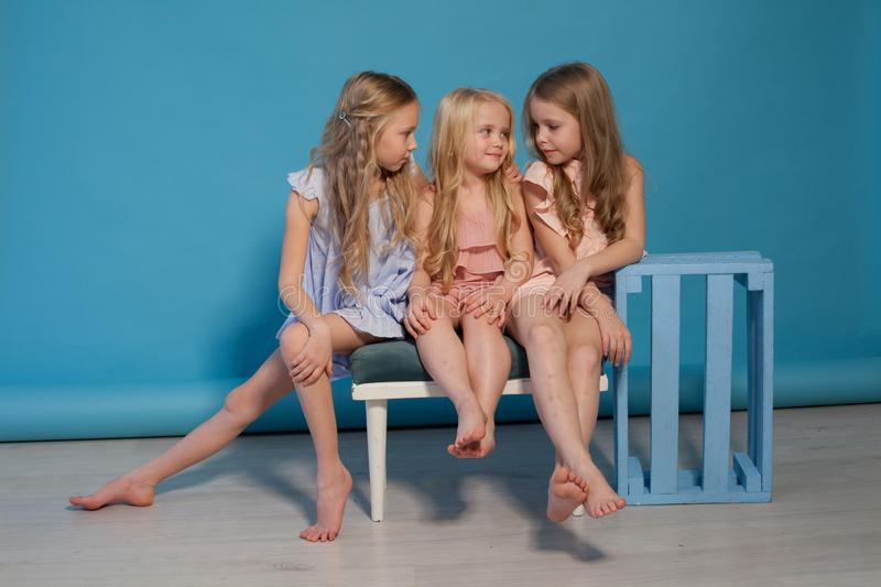 Three beautiful little girls dresses fashion portrait sisters. Blue background royalty free stock photos