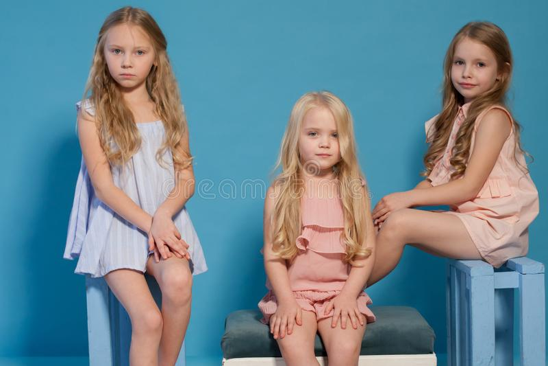 Three beautiful little girls dresses fashion portrait sisters stock images